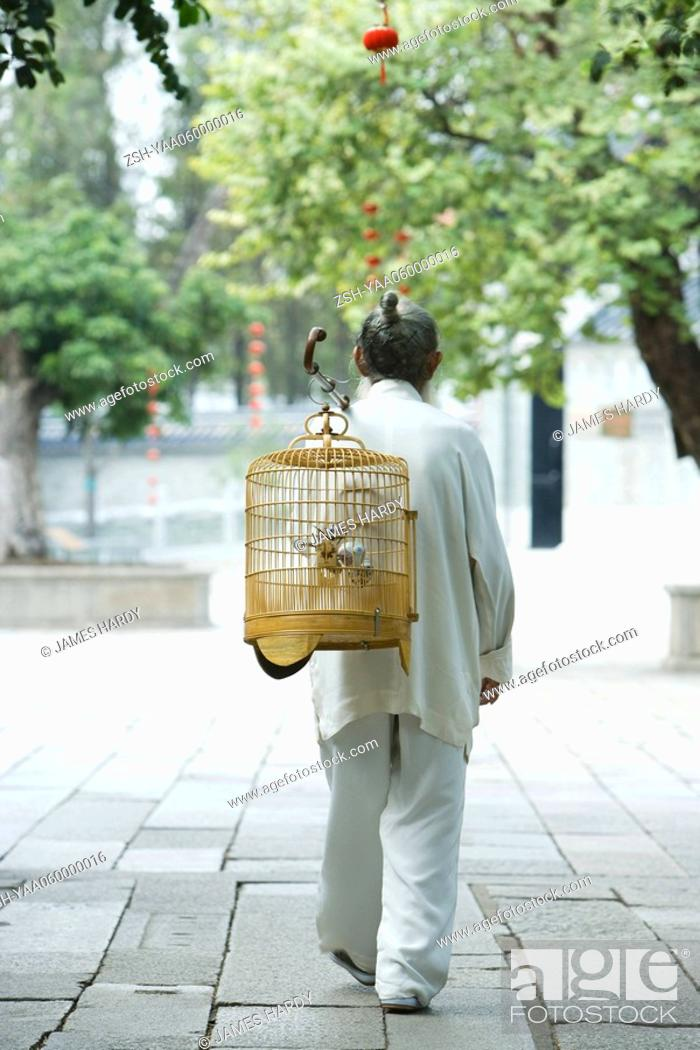 Stock Photo: Elderly man in traditional Chinese clothing, carrying bird cage over back, rear view.