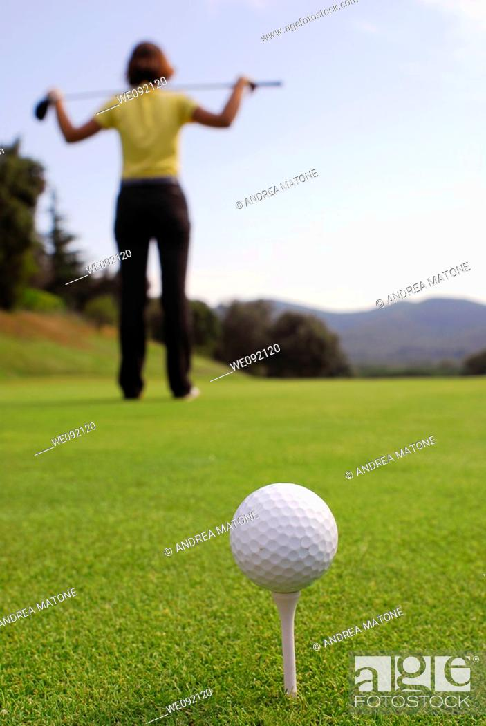 Stock Photo: Young woman golfer observing terrain and conditions before hitting.