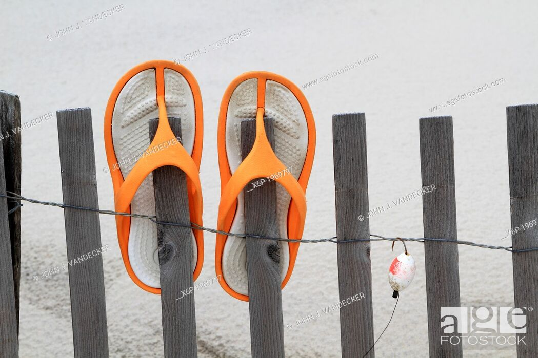 Stock Photo: Flip Flops and fishing lure hanging on a beach dune fence. Lavalette, New Jersey, USA.