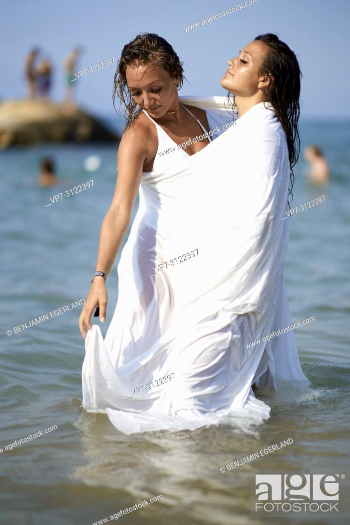 Stock Photo: two sensual women shrouded in white blanket sheet, in sea, best friends, friendship goals, holidays. Chersonissos, Crete, Greece.