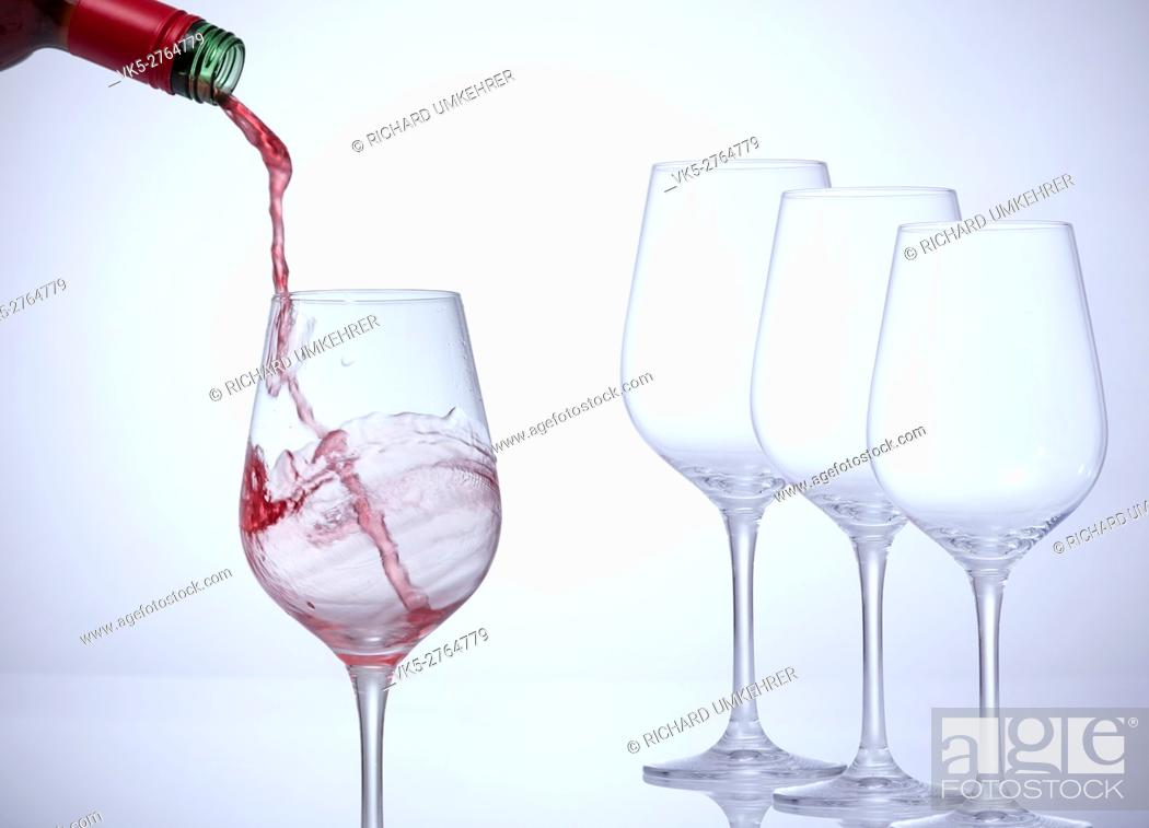 Stock Photo: Motion picture of a man hand fill a glass with wine. Three empty glasses stand in a row. . Against a white background and a vignette.