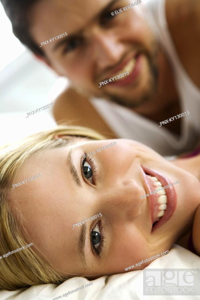 Stock Photo: Young smiling couple in bed.