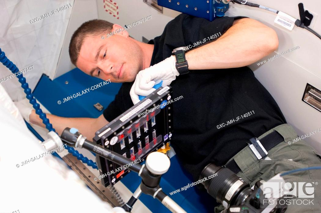 Stock Photo: NASA astronaut Reid Wiseman, Expedition 40 flight engineer, conducts a session with the Binary Colloidal Alloy Test-C1, or BCAT-C1.