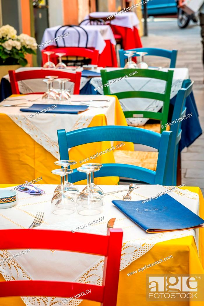 Stock Photo: Tables and chairs of restaurant on the street.
