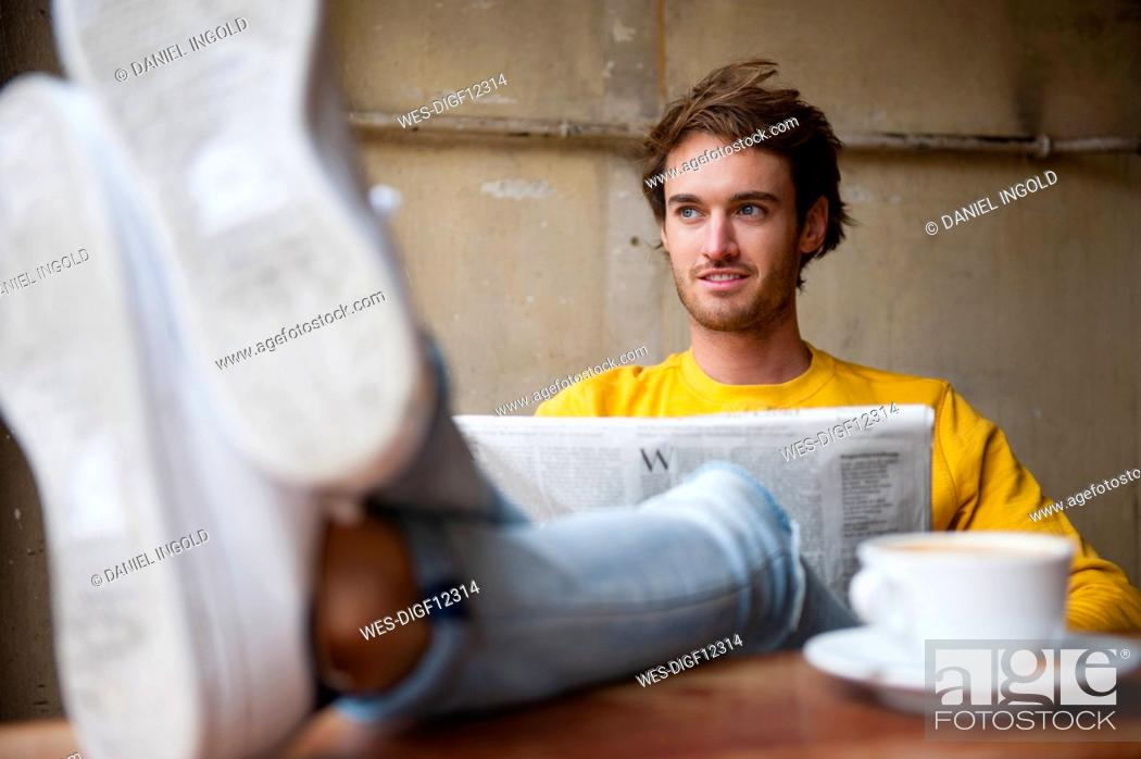 Stock Photo: Portrait of young man with newspaper relaxing with feet up in a coffee shop.