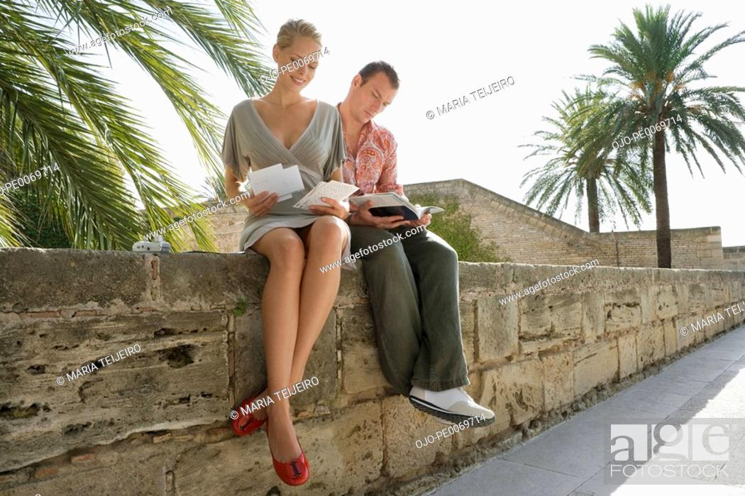 Stock Photo: Man and woman sitting and reading on wall.