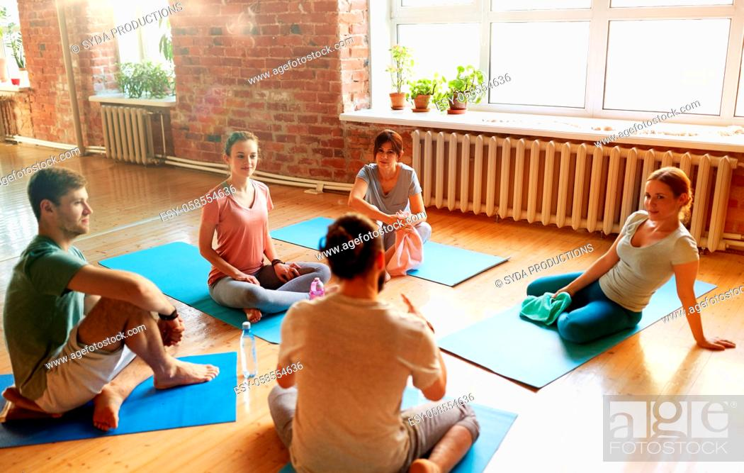 Stock Photo: group of people resting on yoga mats at studio.