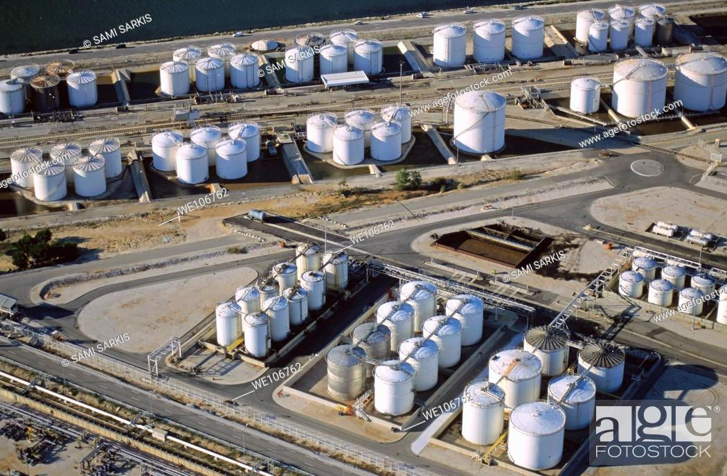 Stock Photo: Oil tanks next to sea with railroad tracks.