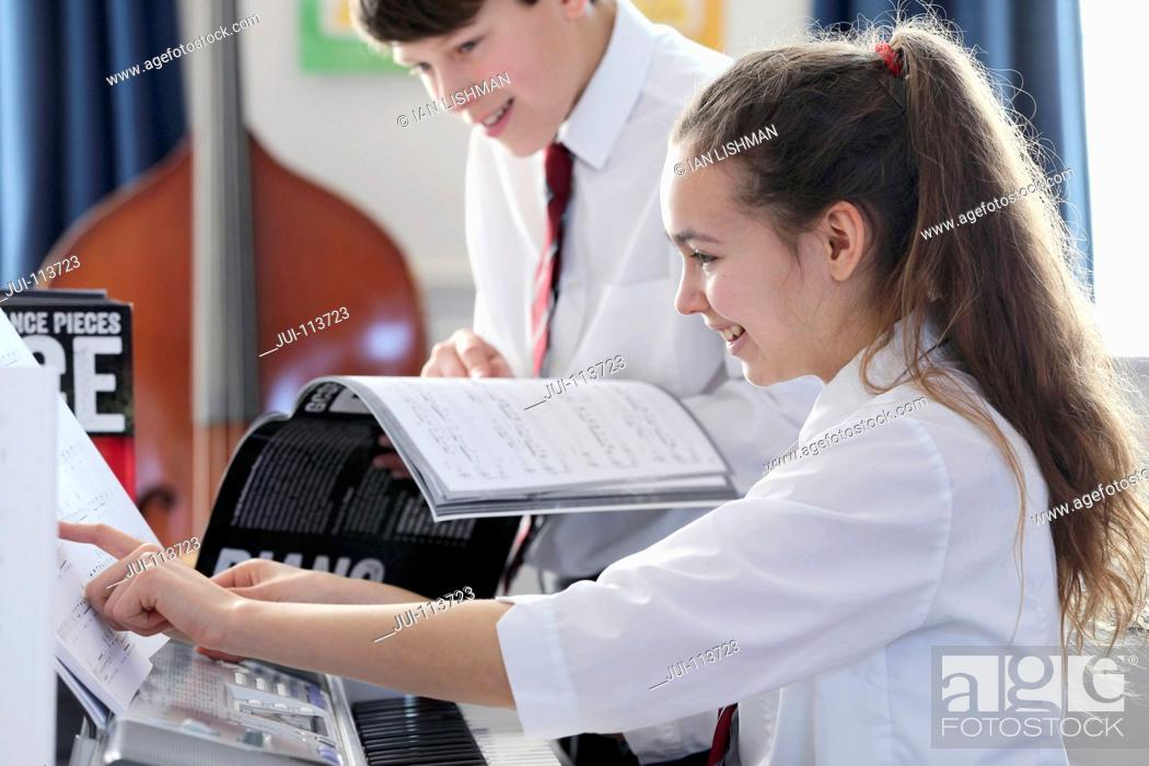 Stock Photo: Highs school students playing piano with sheet music in music class.