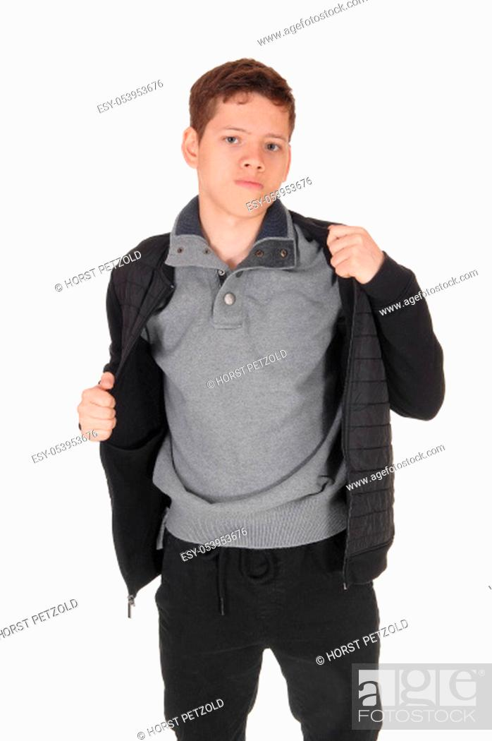 Stock Photo: A close up image of a young teenager boy standing isolated for white .background in the studio, taking his jacket of.