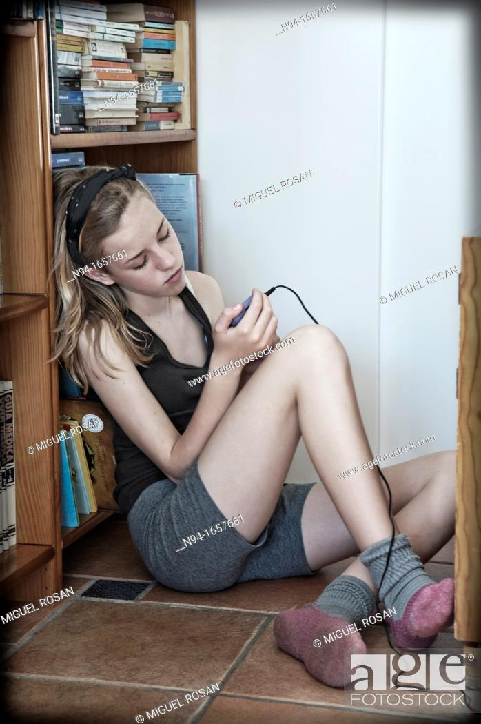 Stock Photo: Teenage girl sitting on the floor of his room, consultation messages from your mobile phone.