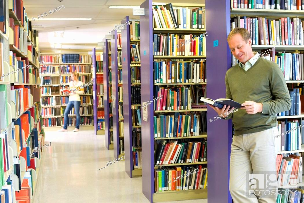 Stock Photo: Man in library looking at book, smiling.