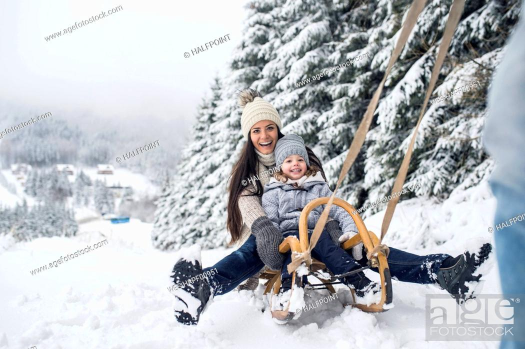 Stock Photo: Happy family with sledge in winter landscape.