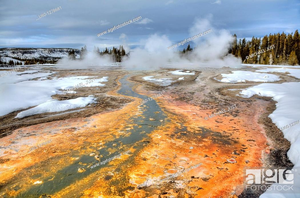 Stock Photo: Boiling water mixes with bacteria and microorganisms to produce high-color amongst the snow at Daisy Geyser at Yellowstone National Park, Wyoming.