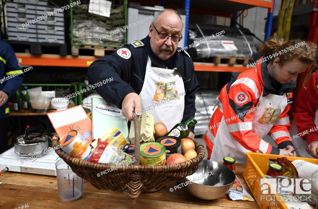 Stock Photo: 19 February 2020, North Rhine-Westphalia, Bonn: Peter Winter, German Red Cross (DRK), lifts a food basket with whose ingredients he will cook.
