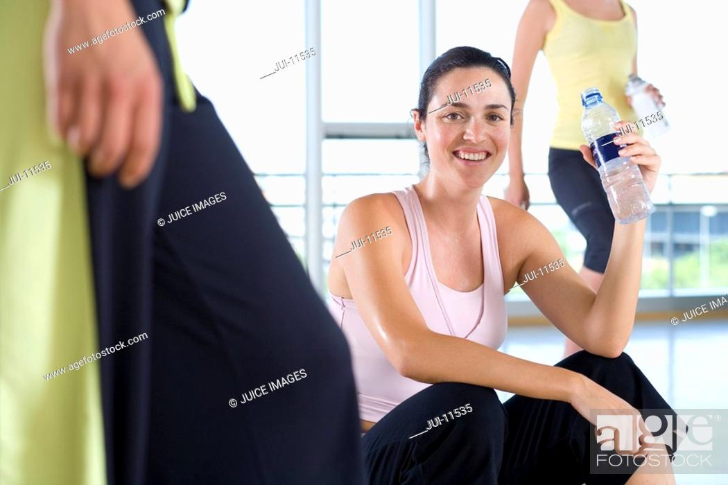 Stock Photo: Woman with water bottle in gym studio, smiling, portrait.