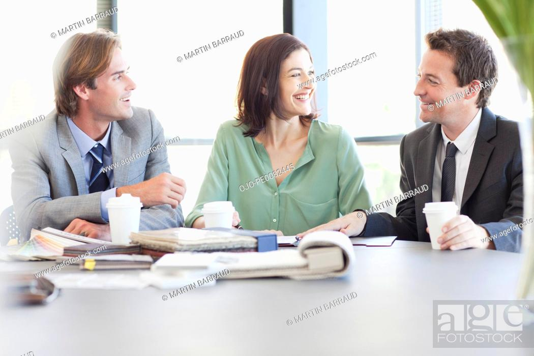 Stock Photo: Business people with coffee talking at table in conference room.