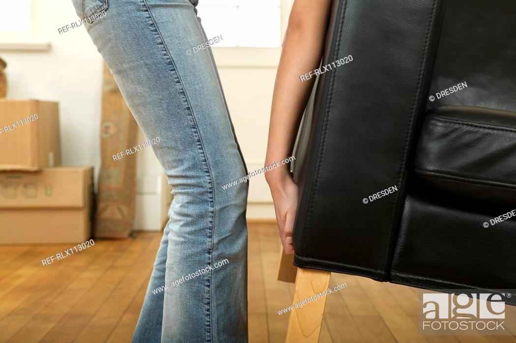 Stock Photo: Young woman moving sofa.