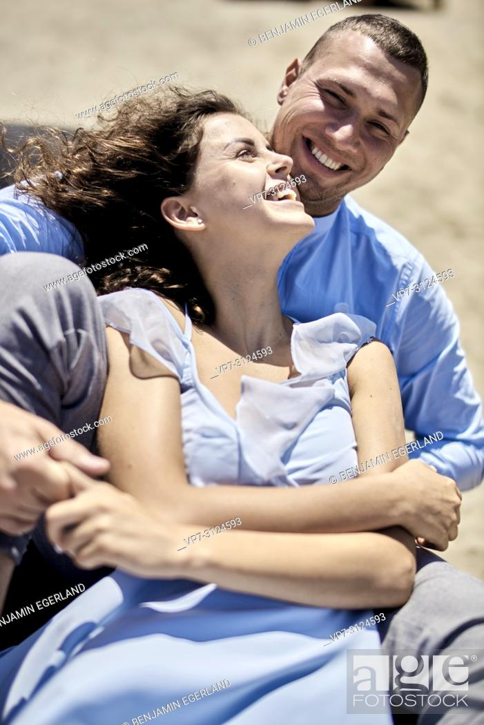 Stock Photo: couple sitting on sunbeds at beach, vacations, summer, love, playful, togetherness, happiness, candid, unposed.