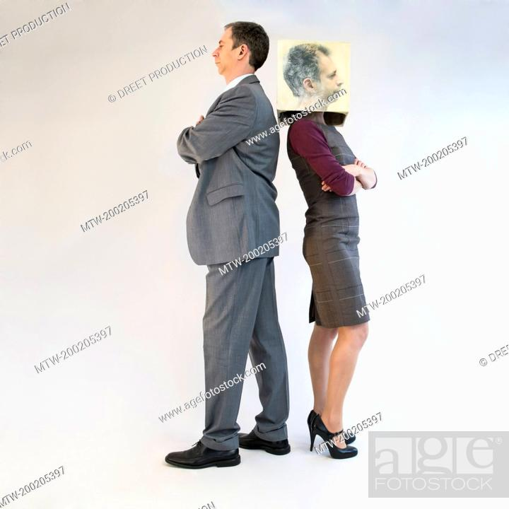 Imagen: Businessman standing back to back of businesswoman wearing mask.