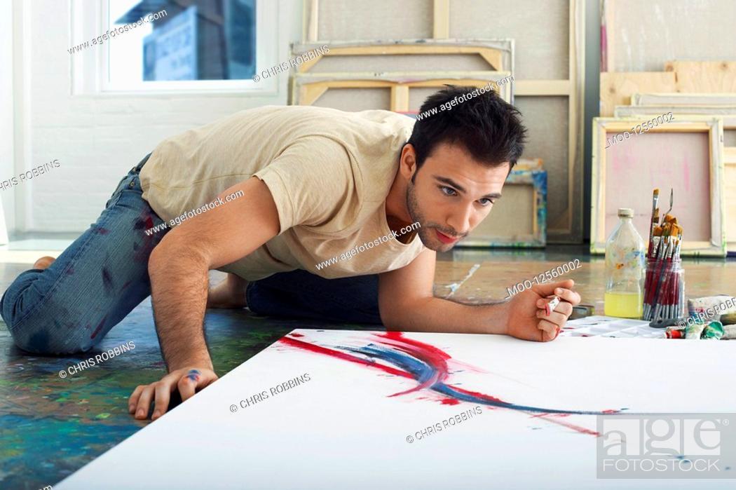 Stock Photo: Artist painting on canvas on studio floor.