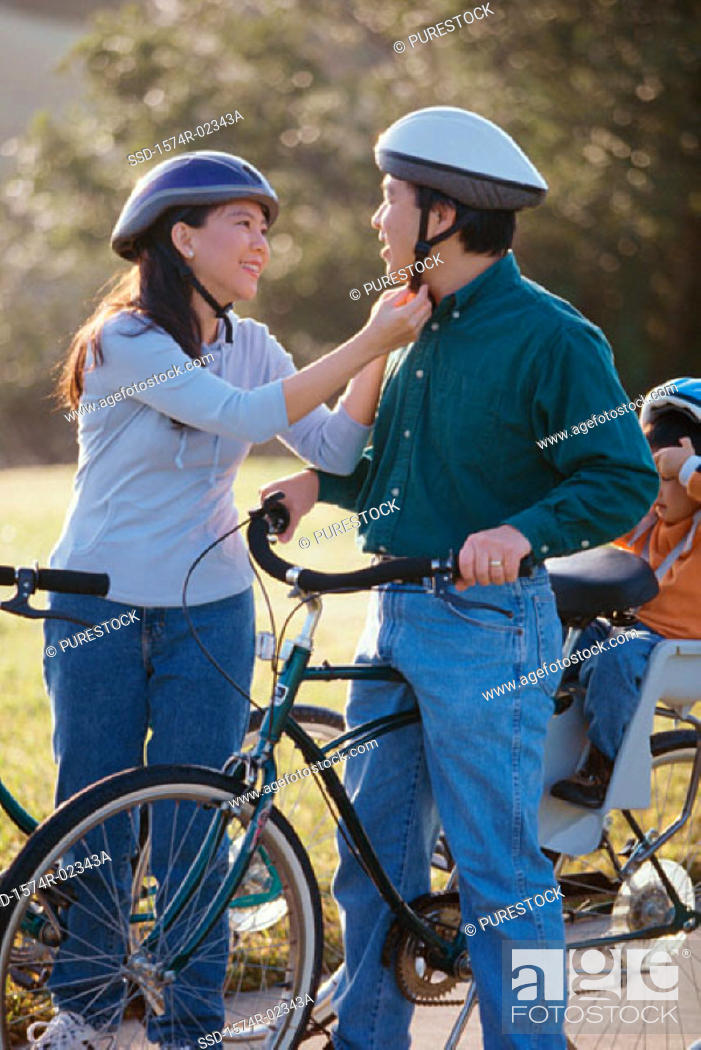 Stock Photo: Parents with their son wearing cycling helmets.