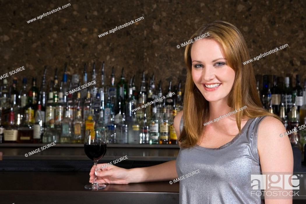 Stock Photo: Smiling woman drinking wine in a bar.