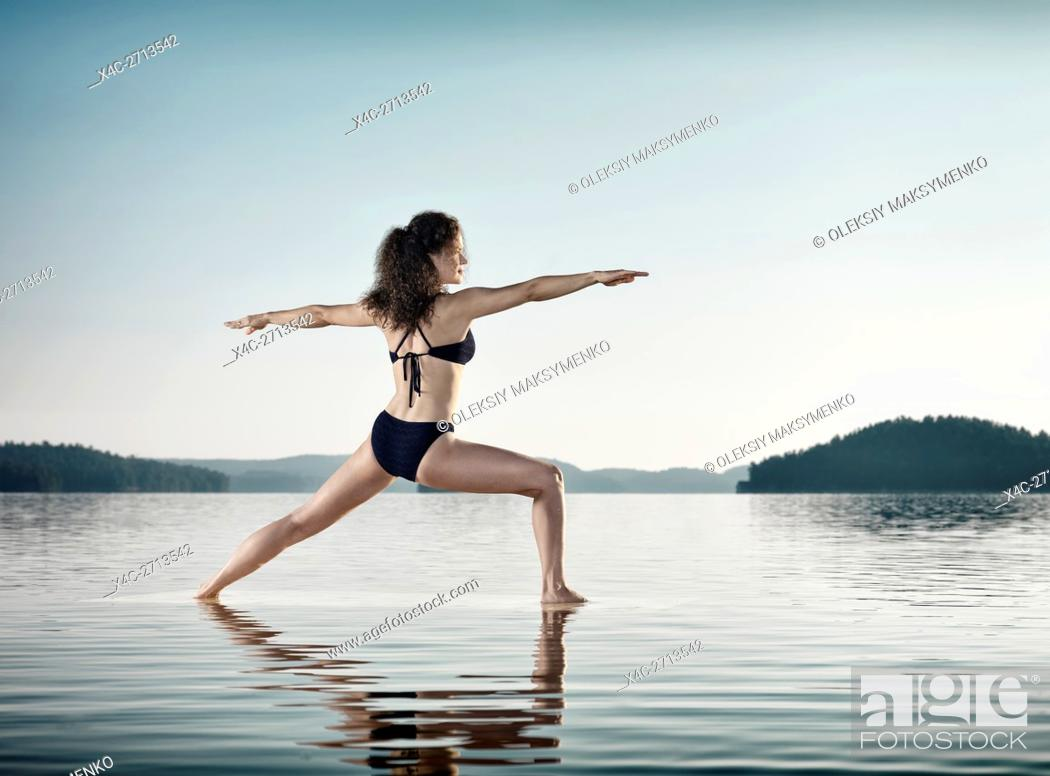 Stock Photo: Young woman practicing Hatha yoga on a floating platform in water on the lake during sunrise in the morning over blue sky background.