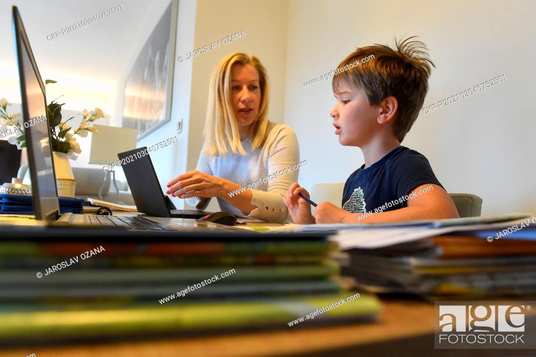 Imagen: Schoolboy of first class with his mother in action during the distance teaching (online education, e-learning, studying via video conference) due to coronavirus.