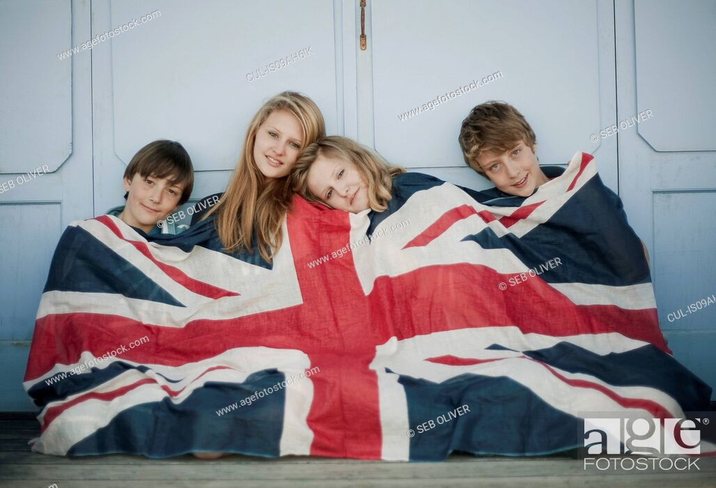 Stock Photo: Portrait of brothers and sisters sitting on porch wrapped in union jack flag.