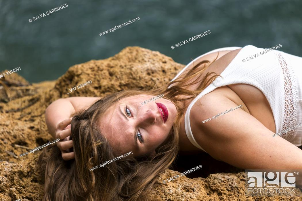 Stock Photo: Woman lying on the rock by the river wearing a white swimsuit.