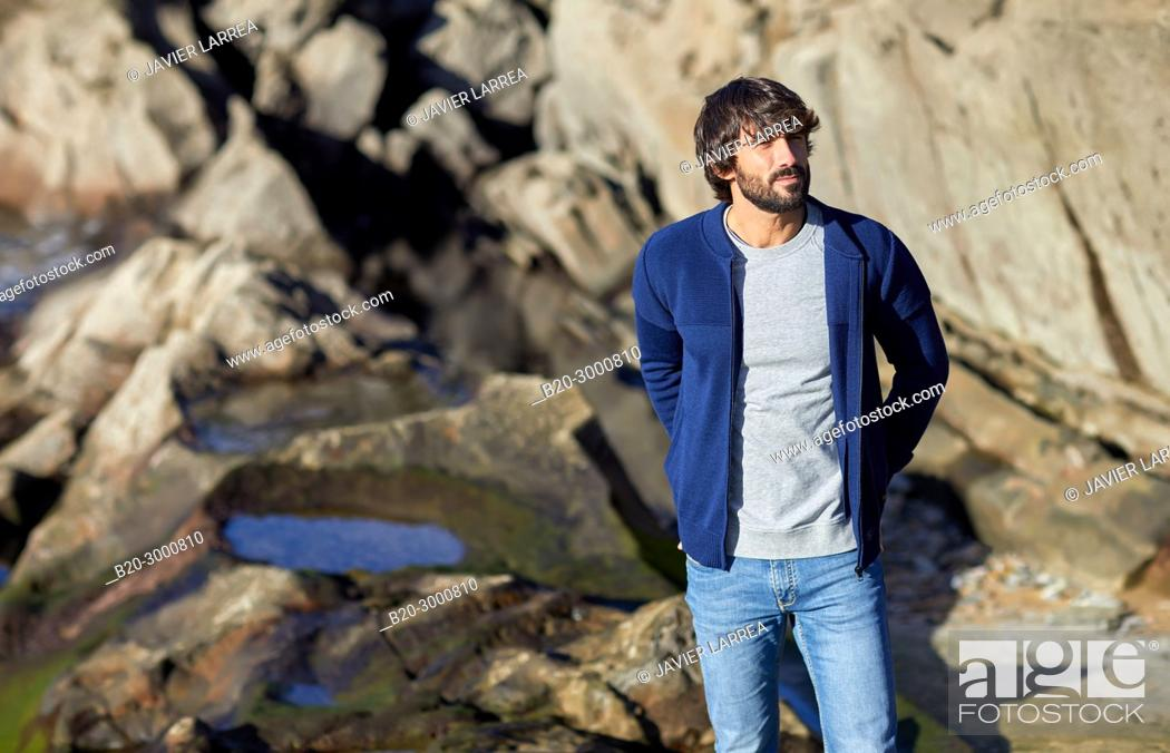 Photo de stock: Adult man at the coast of Santa Clara Island, Donostia, San Sebastian, Gipuzkoa, Basque Country, Spain, Europe.