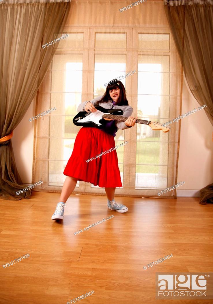 Stock Photo: Teenage girl playing the guitar.