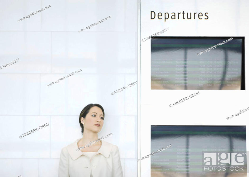Stock Photo: Woman leaning against wall by departure board.
