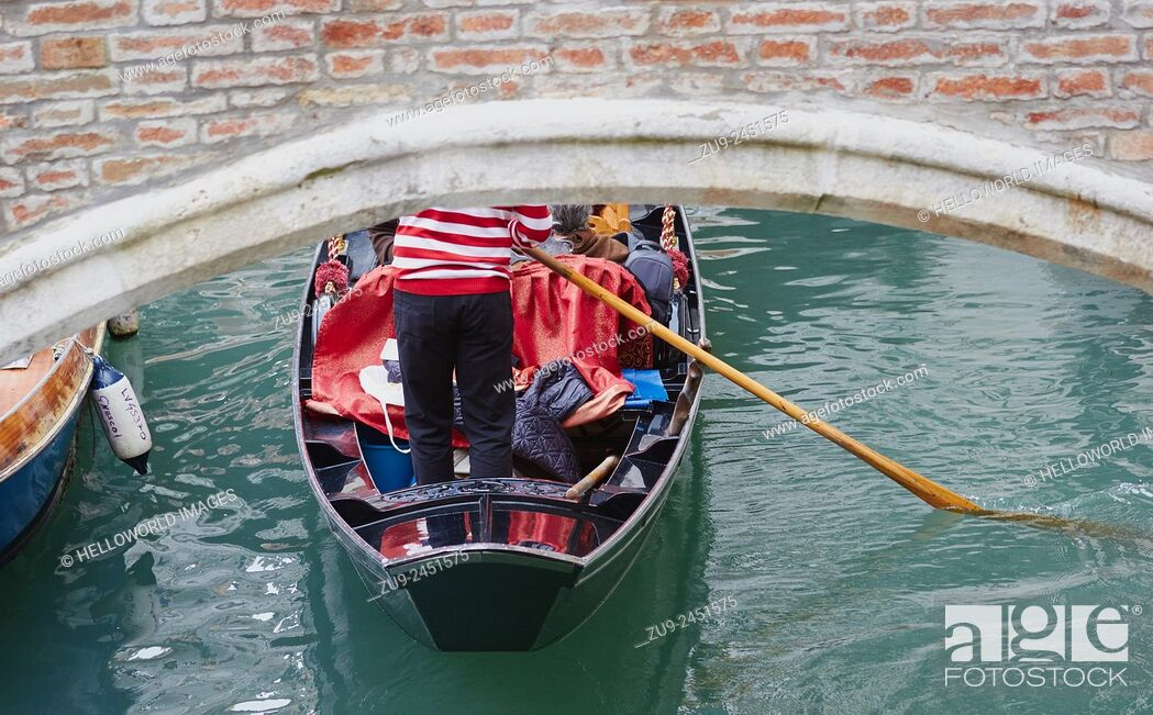 Stock Photo: Gondolier in traditional red and white striped top rowing a gondola under a bridge, Castello, Venice, Veneto, Italy, Europe.