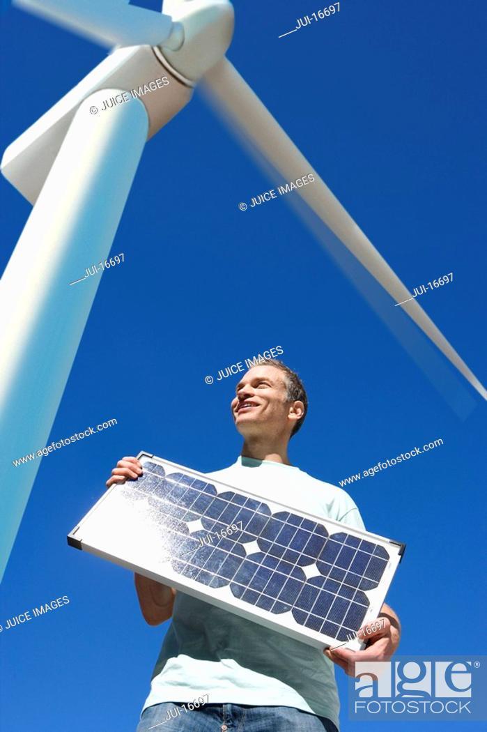 Stock Photo: Man holding solar panel under windmill.