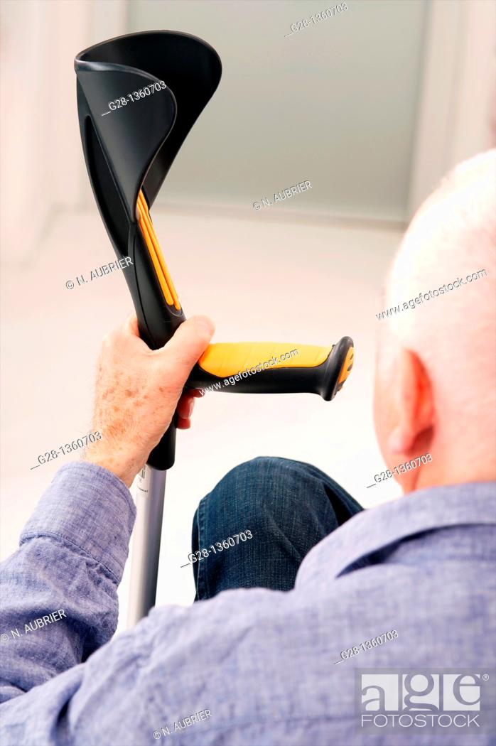 Stock Photo: Senior man seen from behind waiting with his hand on a crutch in a clinic waiting room or medical center.