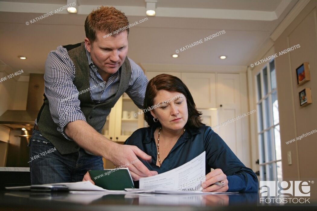 Stock Photo: Husband is angry as married couple pays their bills and reviews their finances together.