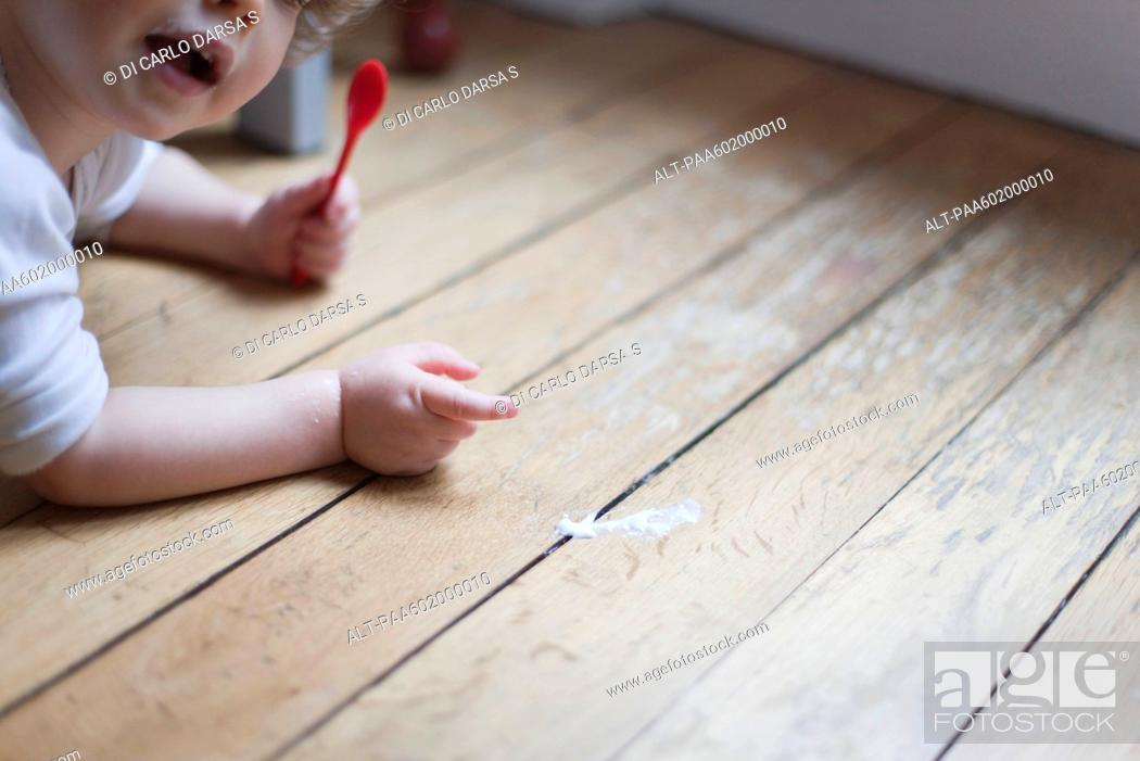 Stock Photo: Toddler lying on floor with spoon in hand, pointing to spilled food.