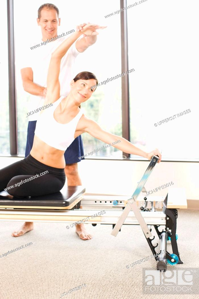 Stock Photo: Personal trainer guiding grimacing woman on pilates equipment.