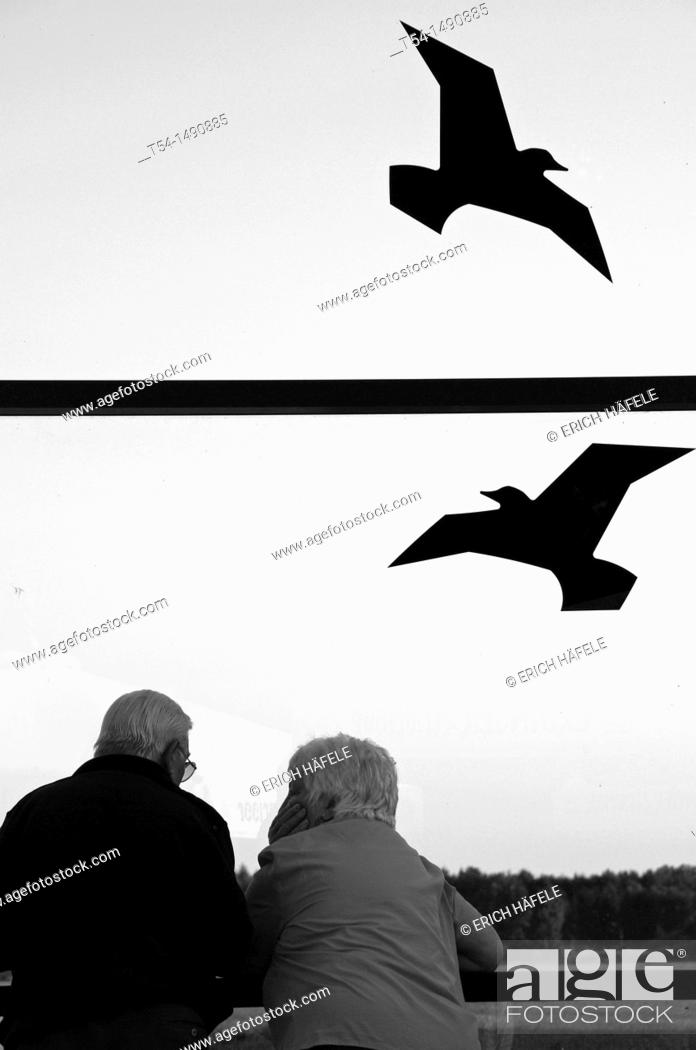 Stock Photo: A couple stands at the airport and watch airplanes.