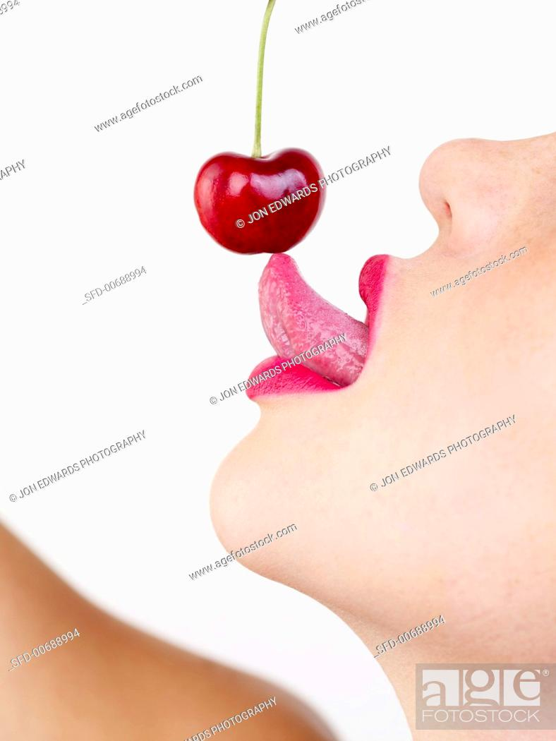 Stock Photo: Woman with Cherry on her Tongue.