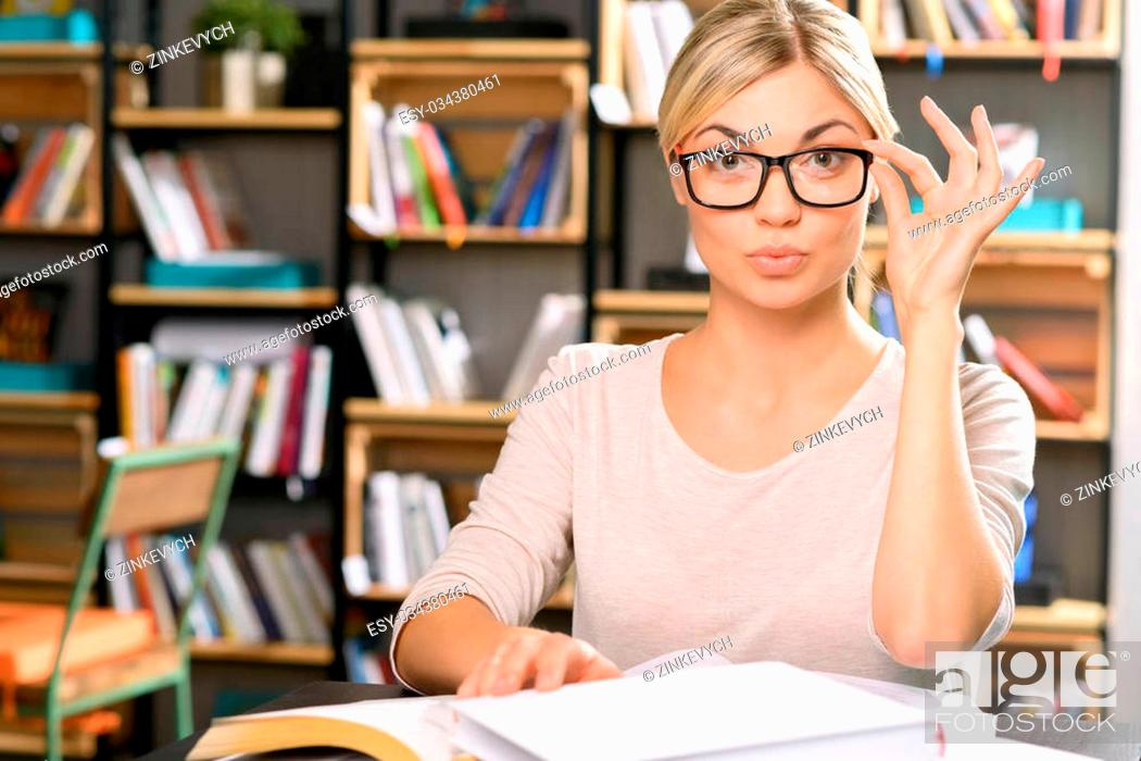 Stock Photo: Nice-looking professional. Young appealing woman is busy with library work.