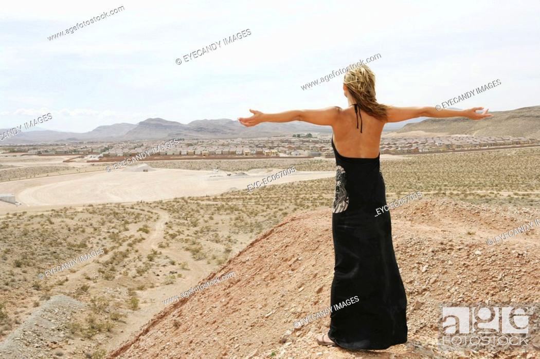 Stock Photo: Caucasian woman in the desert with her arms outstretched.