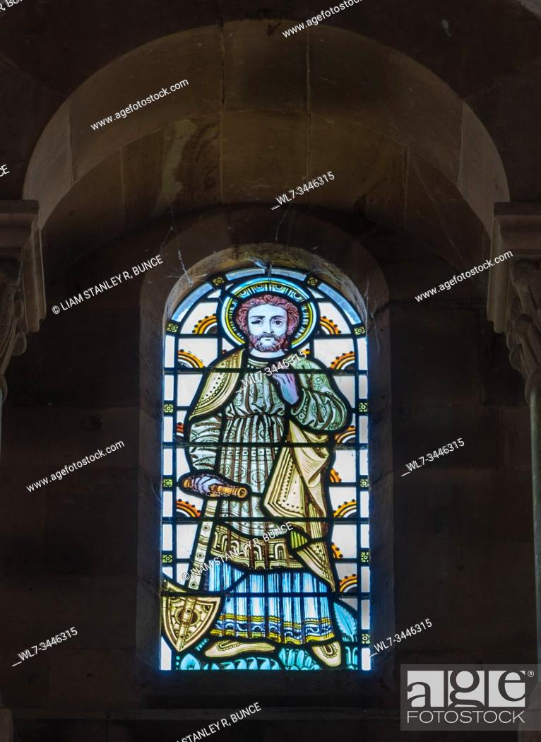Stock Photo: Stained glass possibly Adam delving west wall of St Catherine church Hoarwithy Herefordshire UK. February 2019.