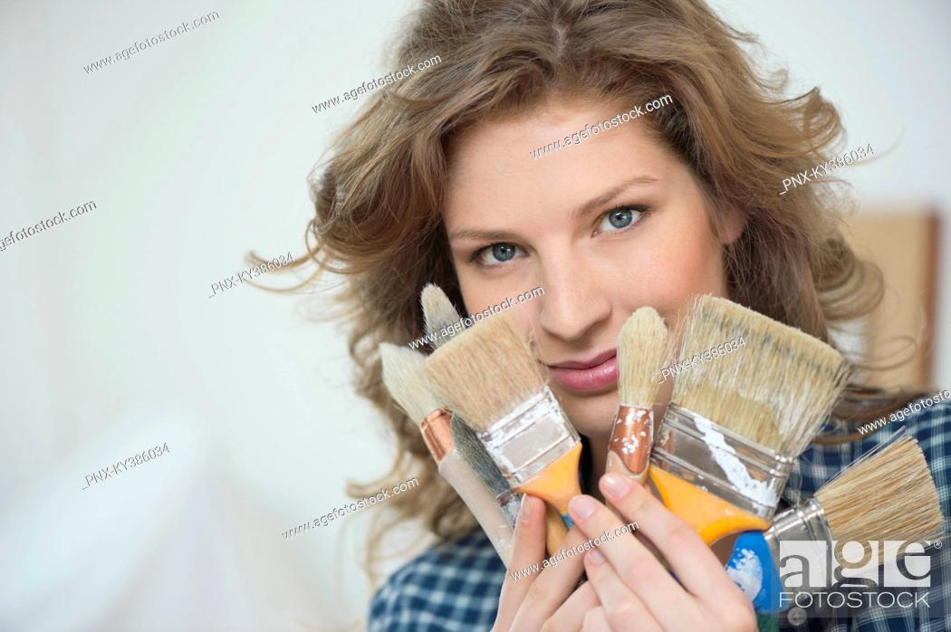 Stock Photo: Portrait of a woman holding paintbrushes.