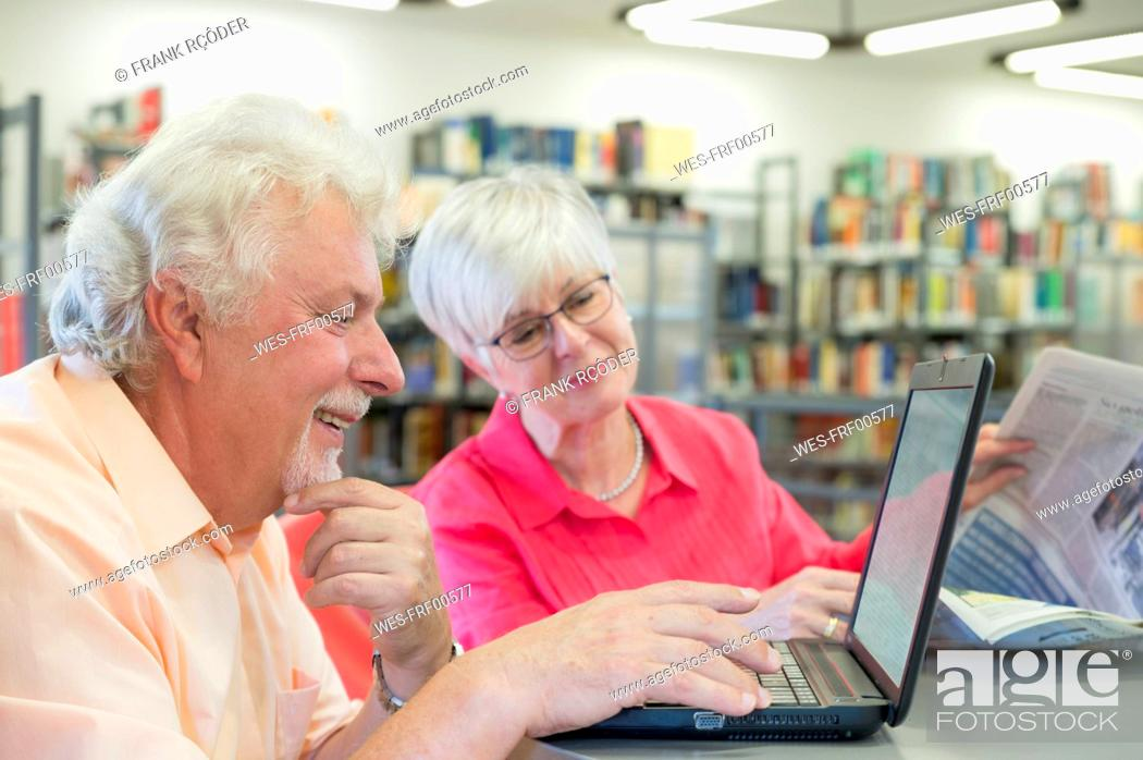 Stock Photo: Senior couple with laptop and newspaper in a city library.