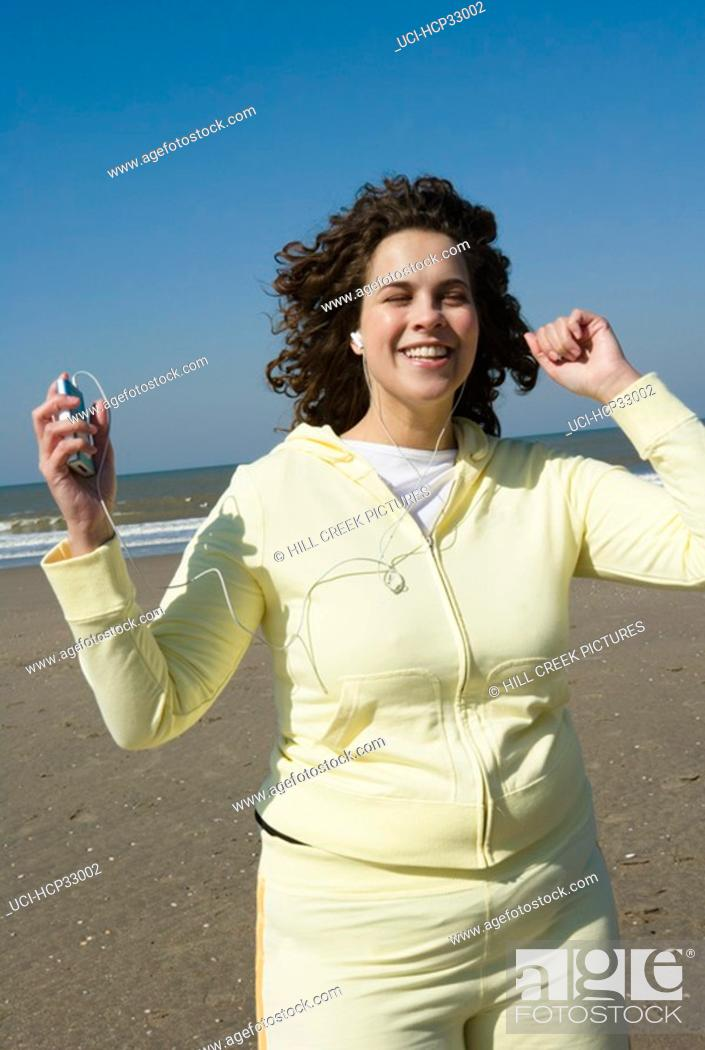 Stock Photo: Woman listening to music, jogging on beach.