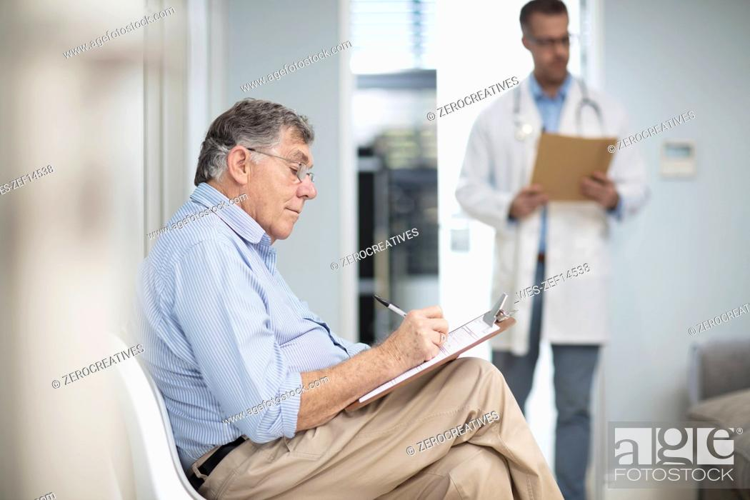 Stock Photo: Patient filling in file in medical practice.