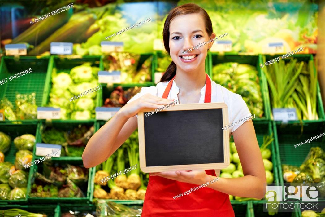 Stock Photo: Germany, Cologne, Young woman with blackboard in supermarket, smiling, portrait.